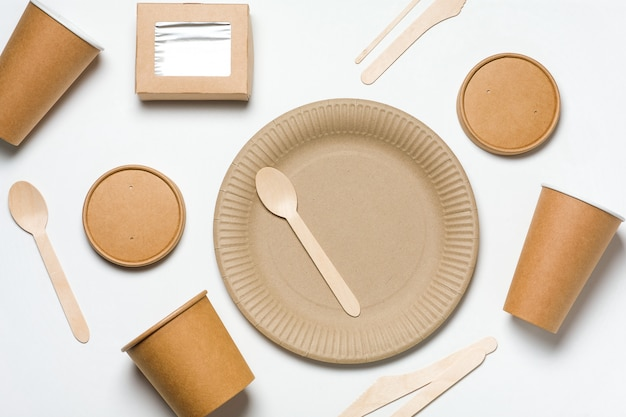Eco-friendly disposable tableware made of bamboo wood and fast food paper on white.