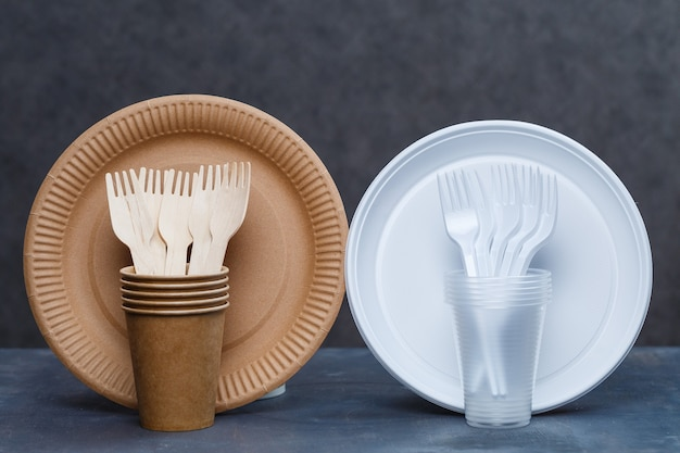 Eco-friendly disposable tableware made of bamboo wood and paper on a gray background. plastic dishes and cutlery. caring for the environment. recycling problem. safe planet, environmental concept.