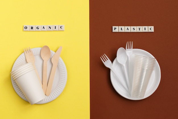 Eco-friendly disposable tableware made of bamboo wood and paper on yellow