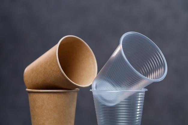 회색 배경에 대나무와 종이로 만든 친환경 일회용 식기. 플라스틱 접시와 칼 붙이. 환경을 돌보는 것. 재활용 문제. 안전한 행성, 환경 개념입니다.
