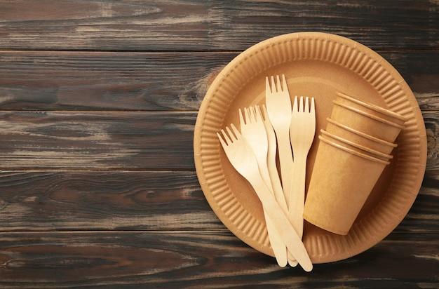 コピースペースのある茶色の背景に環境に優しい使い捨て食器。