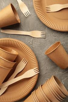 灰色の背景に環境に優しい使い捨て食器。縦の写真