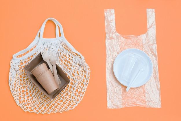 Экологичная одноразовая посуда на экологически чистой сетчатой сумке и пластиковые вредные блюда и столовые приборы на полиэтиленовом пакете.
