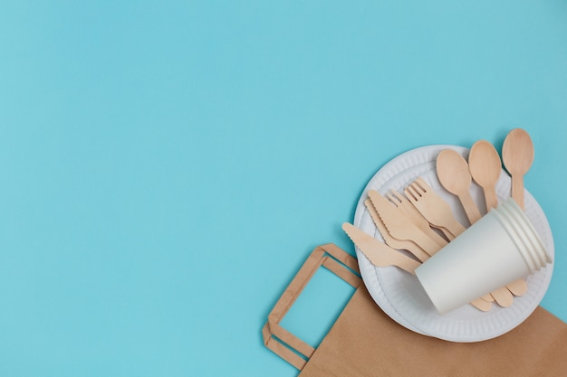 Eco-friendly disposable utensils made of bamboo wood over paper bag on blue background.