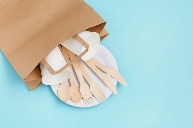 Eco-friendly disposable utensils made of bamboo wood in paper bag on blue background.