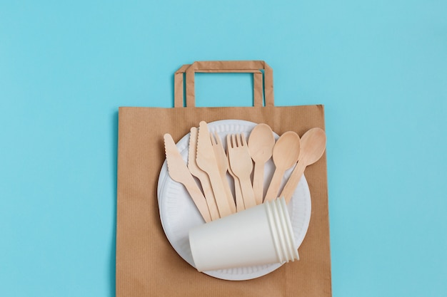 Eco-friendly disposable utensils made of bamboo wood over paper bag on blue.