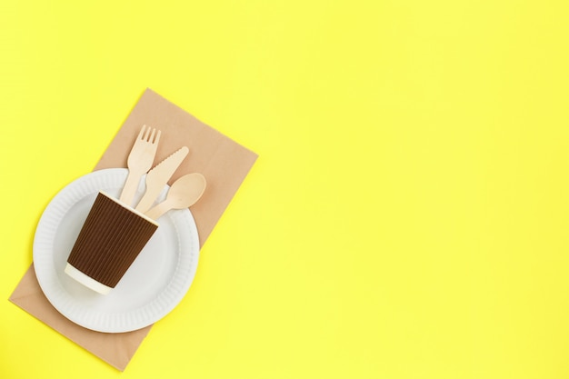 Eco-friendly disposable utensils made of bamboo wood on paper bag on yellow.