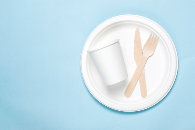 Eco-friendly disposable utensils made of bamboo wood and paper on a blue