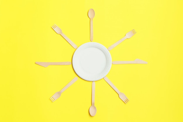 Eco-friendly disposable utensils made of bamboo wood on yellow background.