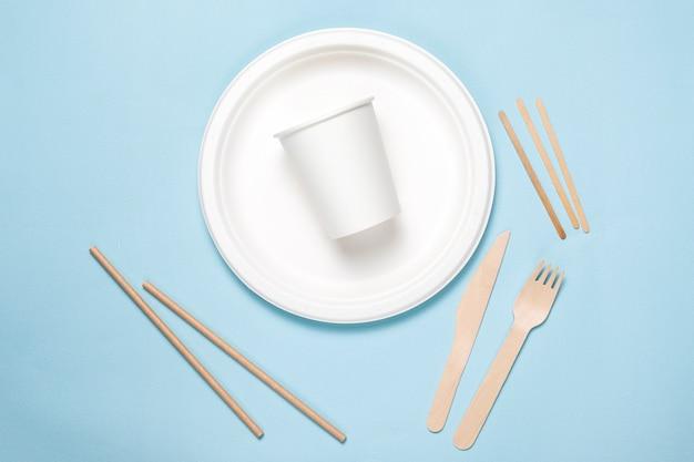 대나무 나무와 파란색 배경에 종이로 만든 친환경 일회용기구. 드레이프 스푼, 포크, 나이프, 종이 그릇과 대나무 그릇.