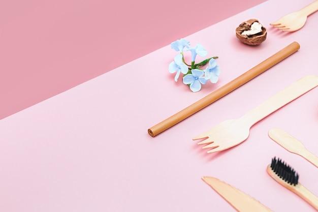 Экологичная одноразовая посуда из бамбука и бумаги на изометрическом розовом фоне. d