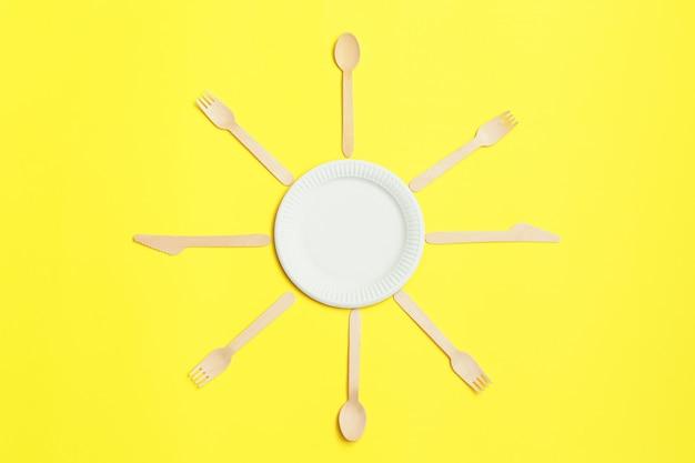 Экологичная одноразовая посуда из бамбука на желтом фоне.