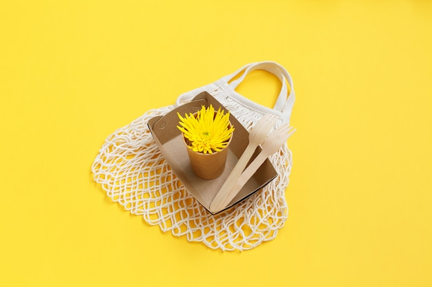 Eco-friendly disposable utensils and mesh textile bag on yellow wall