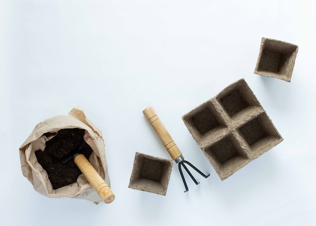 Eco friendly empty pots for seedlings and rakes on white background, small bag with ground and garden trowel