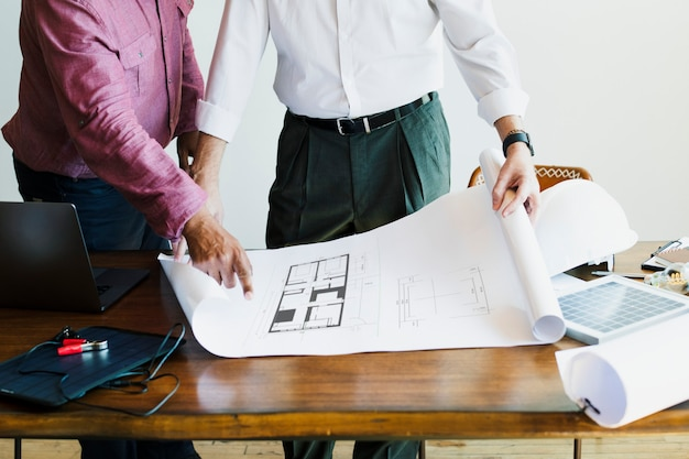 Eco-friendly engineering team looking at a building plan Premium Photo