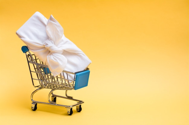 Eco friendly furoshiki gift in a shopping cart on a yellow background. black friday gift sales