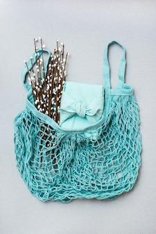 Экологичный подарок - обернутая тканью коробка и букет вербы в сетчатом мешочке на сером фоне. минимализм. синяя палитра