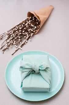 Экологичный подарок - обернутая тканью коробка на тарелке и букет вербы на сером фоне. минимализм. вертикальный вид