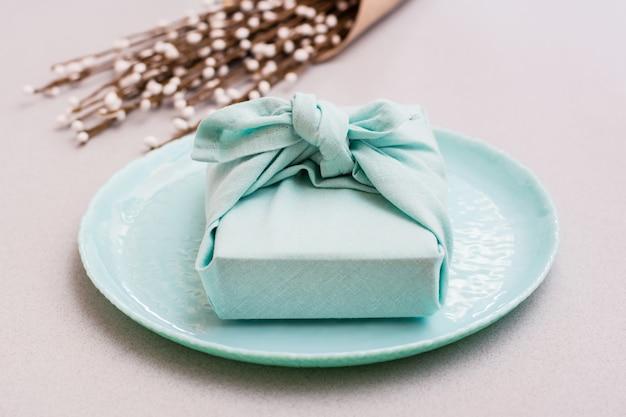 Экологичный подарок - обернутая тканью коробка на тарелке и букет вербы на сером фоне. минимализм.