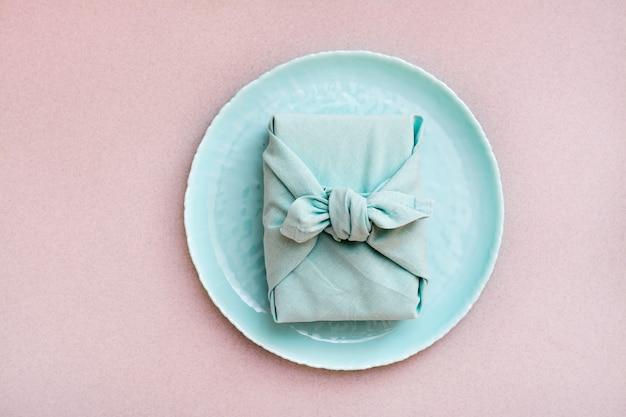 Экологичный подарок - обернутая тканью коробочка на тарелке на сером фоне. минимализм