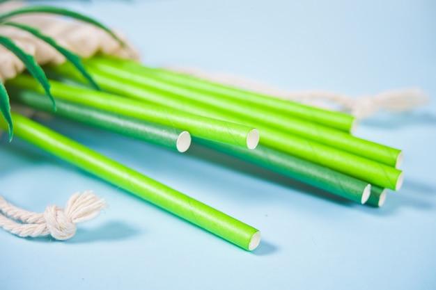 Экологичные зеленые бумажные соломинки в хлопковом мешочке. экологическая концепция. ноль отходов. вид сверху.