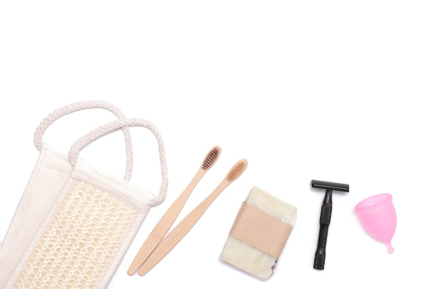 Eco-friendly hygiene items, washcloth, toothbrush, razor, menstrual cup. top view, flat lay.