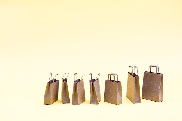 黄色の背景に環境に優しいクラフト紙の買い物袋。ブラックフライデーギフト販売