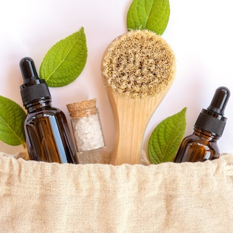 天然木や茶色のガラスとは異なるボトルやバスルームアクセサリーを備えた、環境に優しいリネンの再利用可能なバッグ。周りの新鮮な自然の葉。有機、ゼロウェイスト化粧品のコンセプト。