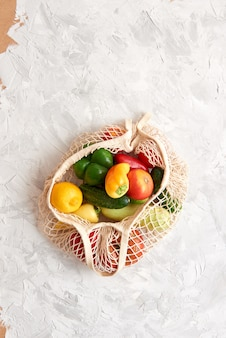 Eco friendly mesh bag with fruit and veggies. top view. no plastic