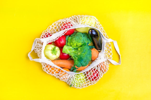Eco friendly mesh shop bag with organic green vegetables on yellow. flat lay, top view.