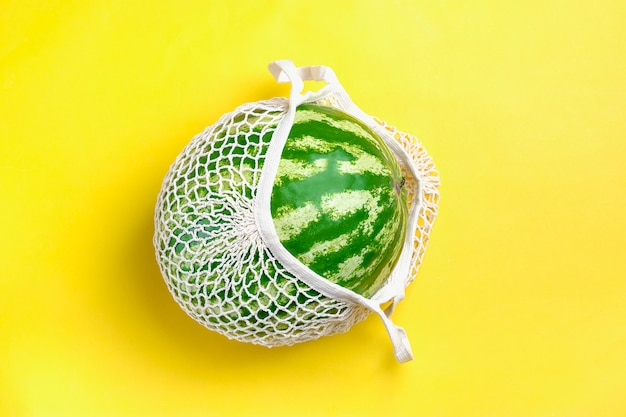 Eco friendly mesh shop bag with organic watermelon on yellow
