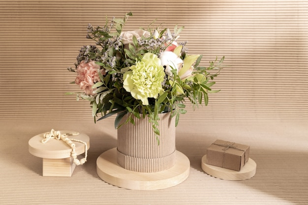 Экологичная монохромная минималистичная композиция с букетом цветов и деревянными подставками разной формы с подарочной коробкой своими руками и бусинами на бежевом с тенями.