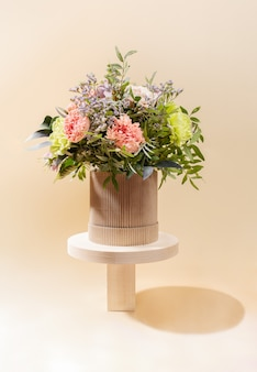 Eco friendly monochrome minimal vertical composition with flowers bouquet standing on wooden stands of different forms on beige with shadows.