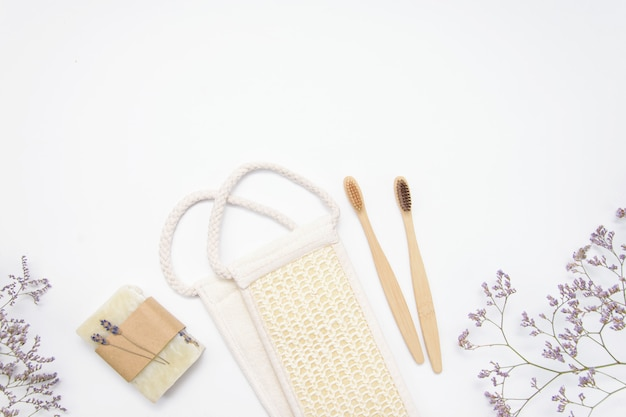 Eco-friendly natural bath sponge, soap and bamboo toothbrushes on a white wall, flat lay, the concept of a healthy lifestyle