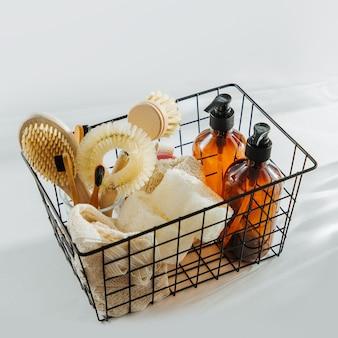 검은색 금속 바구니에 담긴 친환경 천연 청소 도구 및 제품, 대나무 접시 브러시 및 비누