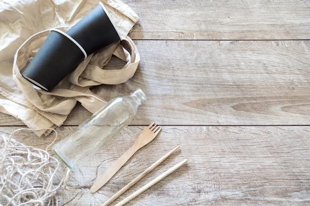 Экологичная органическая одноразовая посуда, стеклянная бутылка, сумка и бумажные стаканчики, вилка на деревянном фоне с копией пространства. переработка, без концепции пластика.