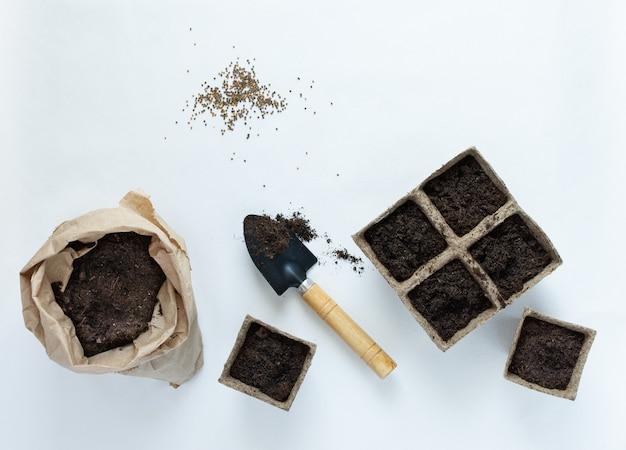 白い背景の苗と種子のための環境にやさしいポット、地面と庭のこてが付いている小さなバッグ