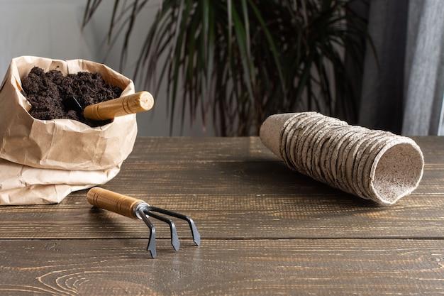 나무 배경에 묘목을 위한 친환경 냄비, 땅과 정원 흙손 및 갈퀴가 있는 작은 가방