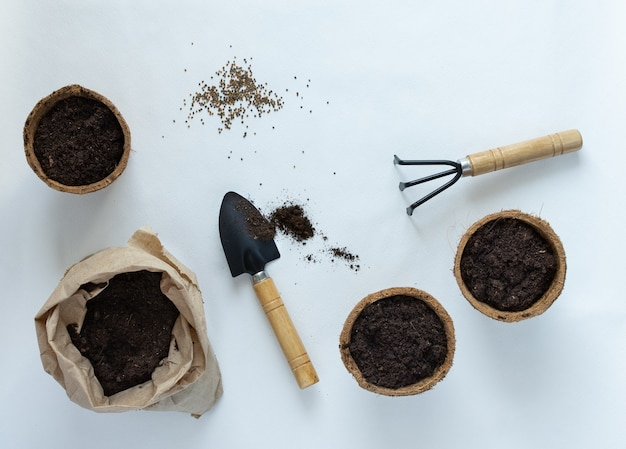 Eco friendly pots for seedlings and seeds on white background, small bag with ground and garden trowel and rakes