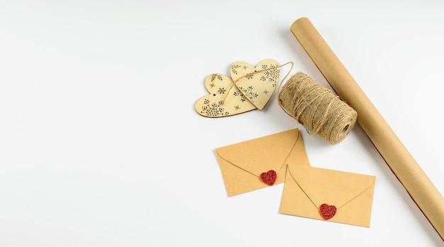 Экологически чистая переработанная крафт-бумага, лента, envilopes и декоративные сердечки на белом фоне