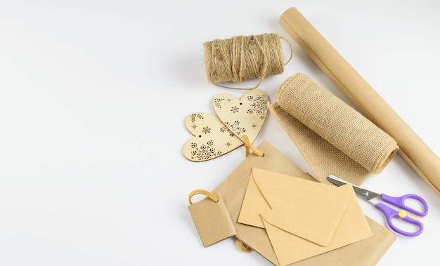 環境にやさしいリサイクルクラフト紙、装飾的なハート、リボン、お祭りの贈り物を作るために用意された封筒。 diyのコンセプト。フラットレイ、上面図。