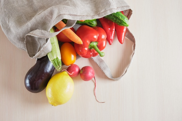 Eco friendly reusable mesh string knitted shopping bag with fruits and vegetables on the table, zero waste concept