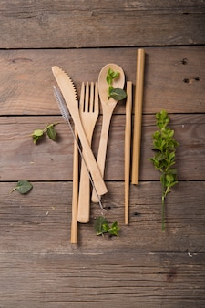 環境に優しい再利用可能な金属のストローとカトラリー(スプーン、ナイフ、フォーク)の木製のテーブル。廃棄物ゼロのコンセプト