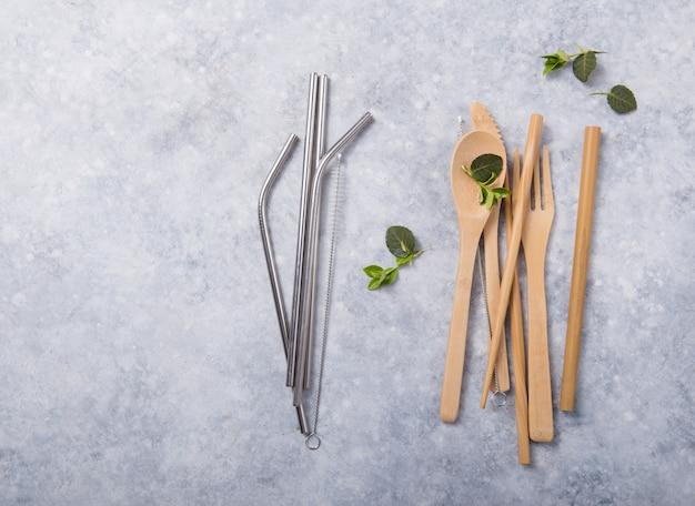 環境に優しい再利用可能な金属のストローとカトラリー(スプーン、ナイフ、フォーク)の木製のテーブル。廃棄物ゼロのコンセプト Premium写真