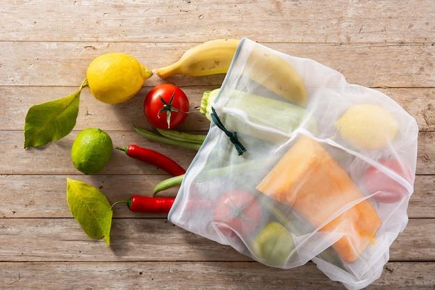 Экологичная многоразовая сумка для покупок с овощами и фруктами на деревянном столе