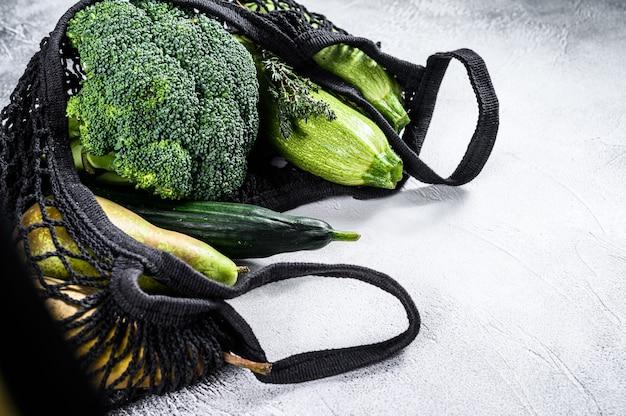 野菜がいっぱい入った、環境にやさしい再利用可能なショッピングストリングバッグ。環境にやさしい、プラスチックを含まない。灰色の表面。上面図。コピースペース