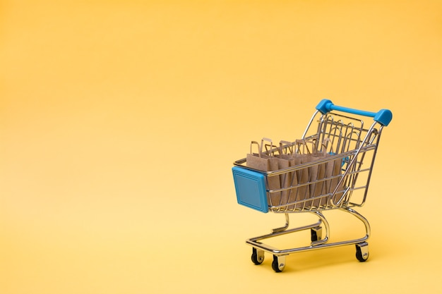 Eco-friendly shopping bags made of craft paper in a shopping cart on a yellow background. black friday gift sales. copy space
