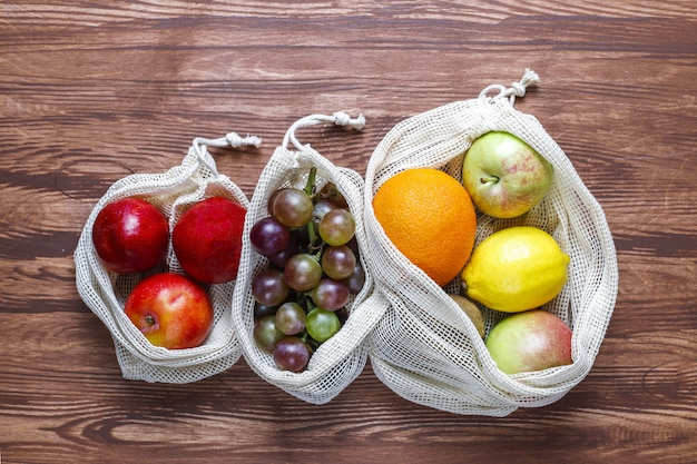 Eco-friendly simple beige cotton shopping bags for buying fruit and vegetables with summer fruits.