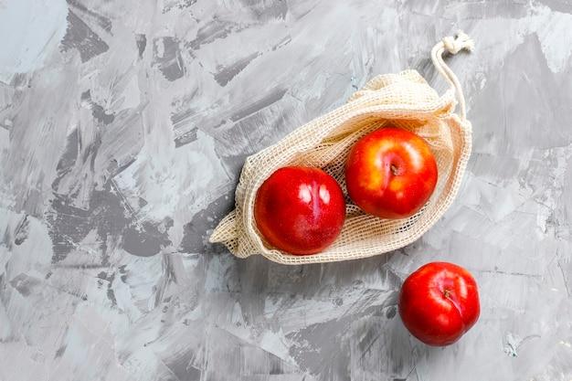 夏の果物と一緒に果物や野菜を買うための環境に優しいシンプルなベージュの綿の買い物袋。
