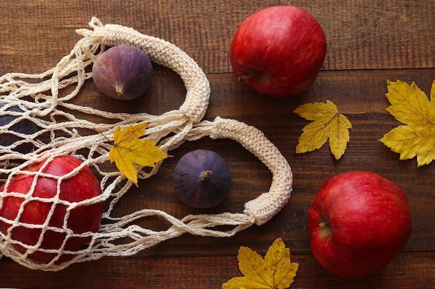 木製の秋にリンゴとイチジクが入った環境に優しいストリングバッグ